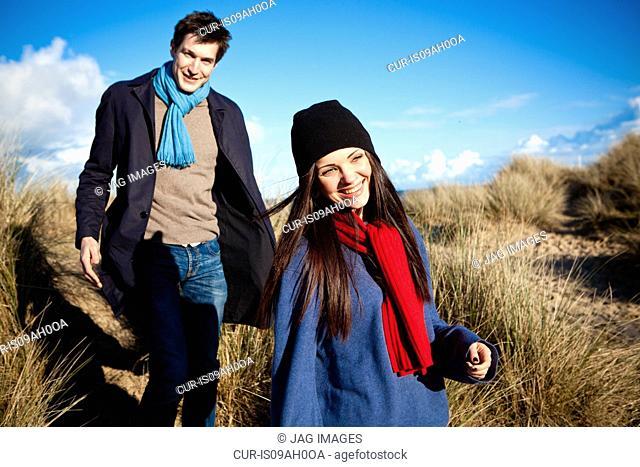 Couple strolling in sand dunes, Bournemouth, Dorset, UK
