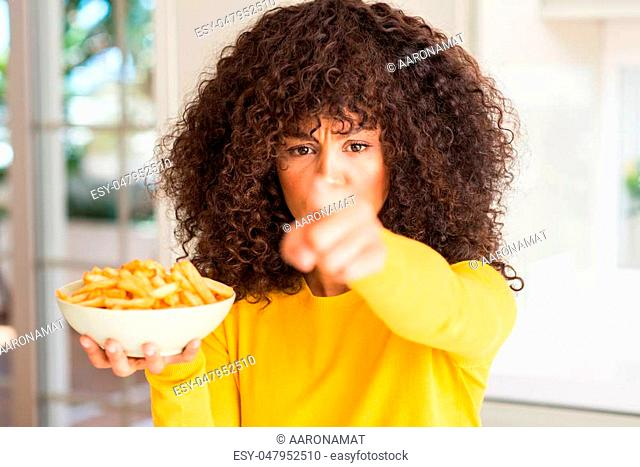 African american woman holding a plate with potato chips at home pointing with finger to the camera and to you, hand sign