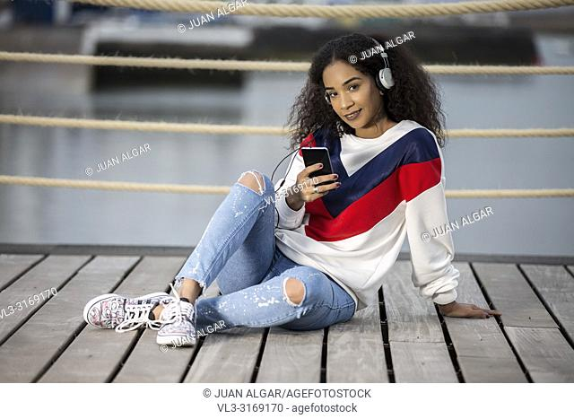 Pretty ethnic girl in stylish casual outfit using headphones with phone and looking flirty at camera