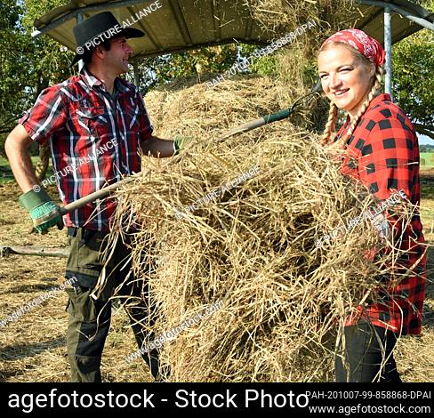 01 October 2020, Saxony, Wermsdorf: Cora Lechner prepares organic hay for her animals in her bison enclosure with her life partner Johannes Boos