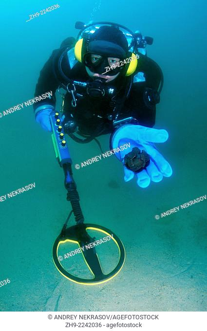 Diver with the metal detector displays the found ancient coins, lake Baikal, Siberia, Russia, Eurasia