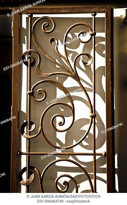Nice wrought iron handicraft door casting shadows, Cordoba, Spain