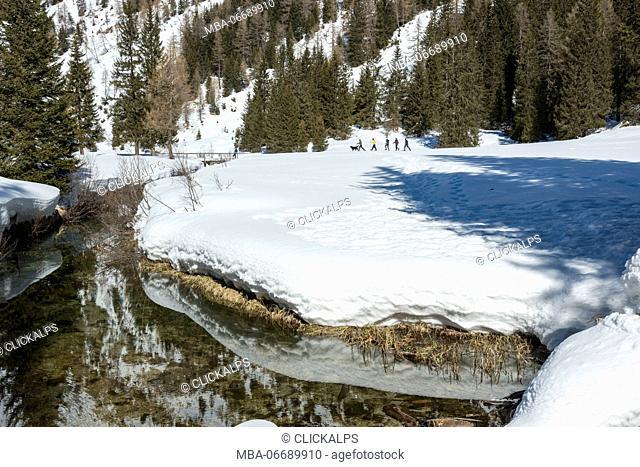 Hikers with snowshoe adventure on the snow towards nambino lake, natural park Adamello Brenta, Madonna di Campiglio, Trentino Alto Adige, Italy, Europe