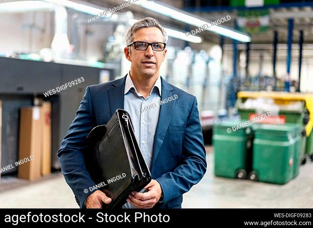 Portrait of a businessman with glasses and briefcase in a factory