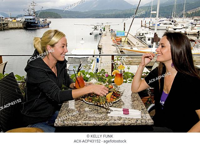 Two young women have lunch at a beautiful seaside restaurant in Sechelt, British Columbia, Sunshine coast, Vancouver coast and mountain range, Canada