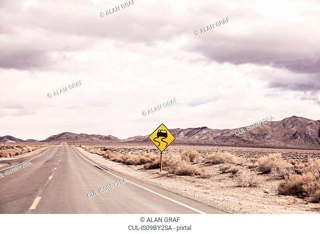 Arid landscape with yellow warning sign on roadside, Keeler, California, USA