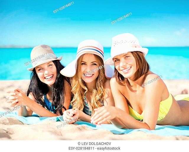 summer holidays, travel, people and vacation concept - happy young women in bikinis sunbathing over exotic tropical beach background