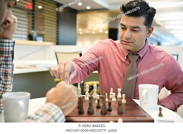 Businessman playing chess with coworker at table