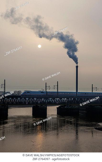Hamburg on a winter morning, stean comes from a smokestack, as the sun comes through a the fog