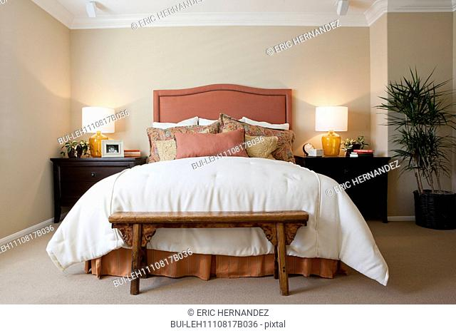 Arranged pillows on tidy bed with lit table lamps in the bedroom at home; California; USA