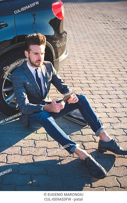 Stylish young man sitting leaning against car with digital tablet
