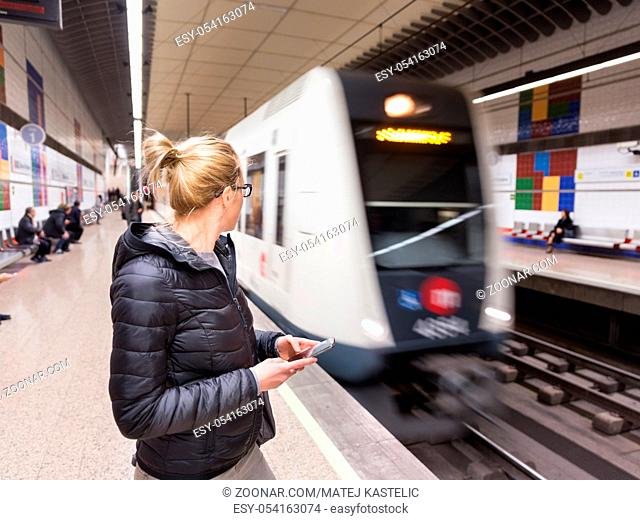 Young casual woman with a cell phone in her hand waiting on the platform of a metro station for metro to arrive. Public transport