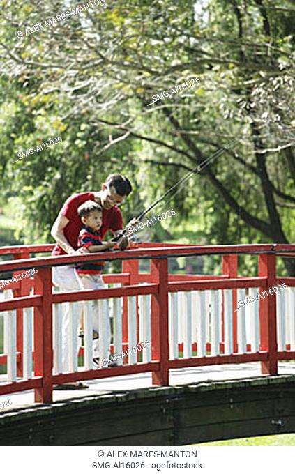 Father and son on bridge, fishing