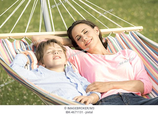 Mother and son lying in hammock, eyes closed, smiling, Germany, Europe