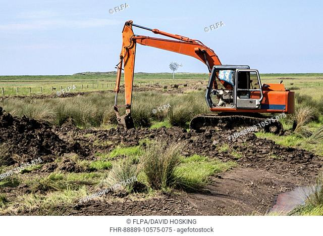 Using a digger excavator for habitat restoration work on Deepdale Marsh, Burnham Deepdale, North Norfolk