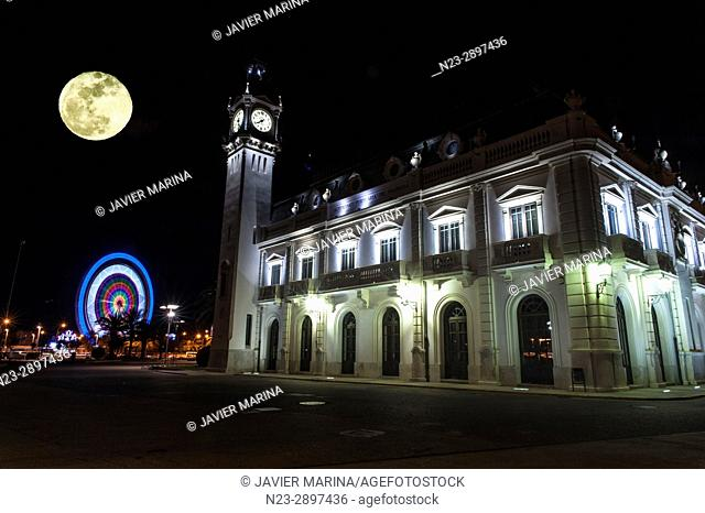 Moon and Port of Valencia Building, Ferris wheel in background. Valencia, Valencian Community, Spain