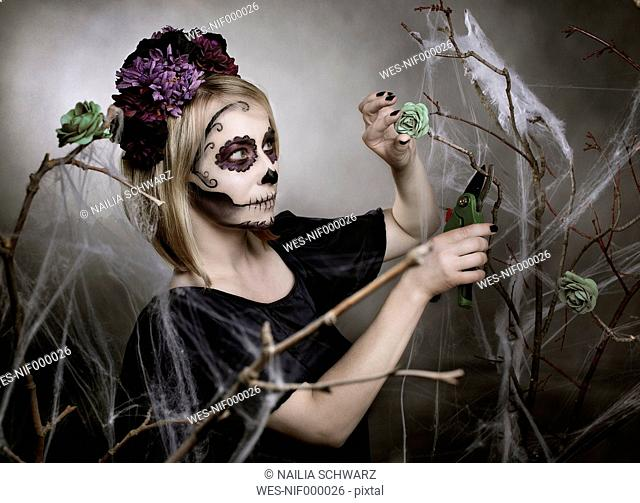 Woman with sugar skull makeup cutting blossom with gardening clipper