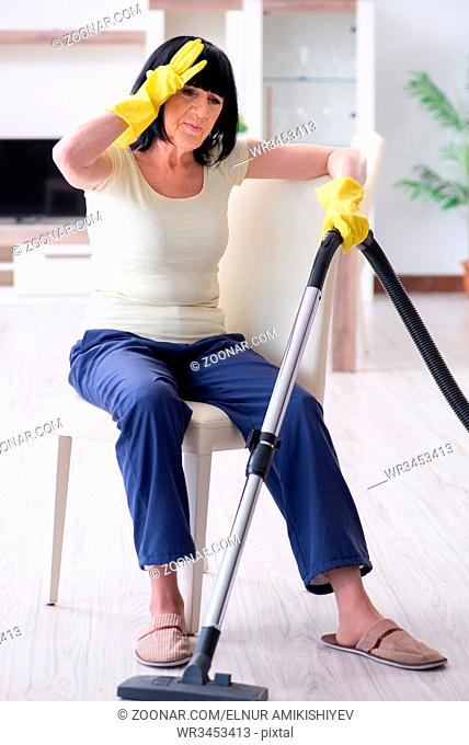Senior old woman tired after vacuum cleaning house