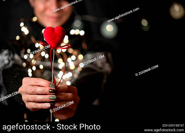 The girl holds red heart in hand on a garland bokeh background