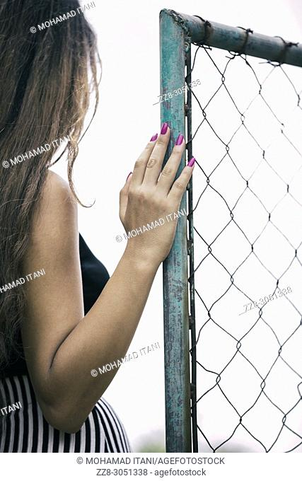 Rear view of a young woman standing by a chicken wire gate
