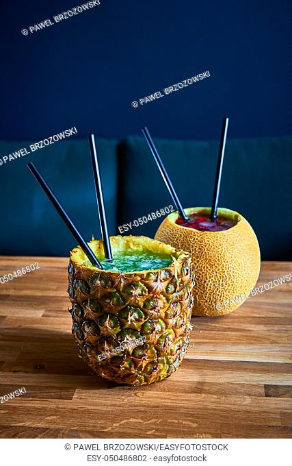 Tropical drinks with ice in pineapple and melon on the wooden table in a pub. Copy space