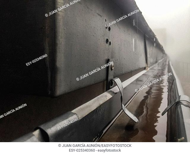 Gutter drainage system on the roof with dripping fog and rain. Closeup