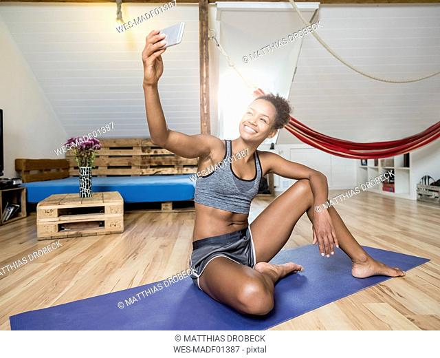 Smiling young woman sitting on yoga mat taking a selfie