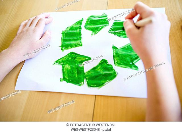 Close-up of girl painting recycling symbol