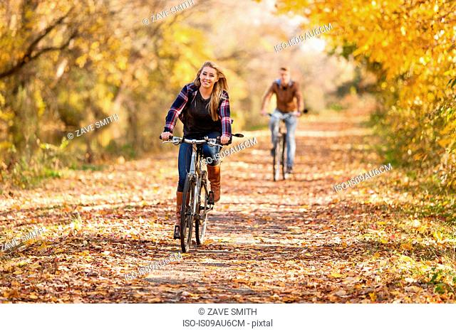 Teenage boy and adult sister cycling in autumn forest