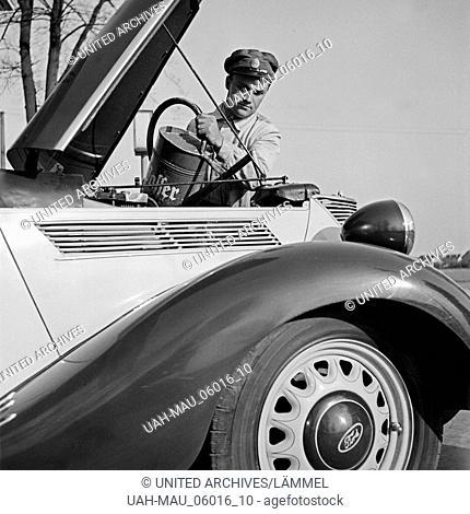 Der freundliche Tankwart füllt Kühlwasser nach, Deutschland 1930er Jahre. Perfect customer service at the petrol station, Germany 1930s