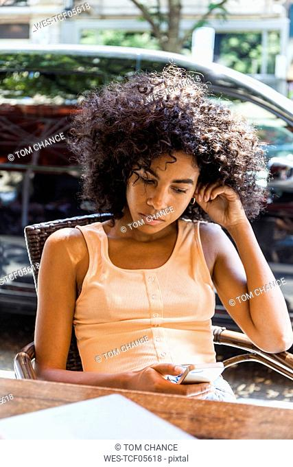Portrait of young woman with curly hair sitting at sidewalk cafe looking at cell phone