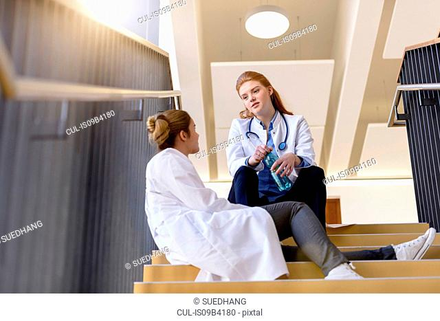 Two female doctors taking a break on hospital stairway chatting