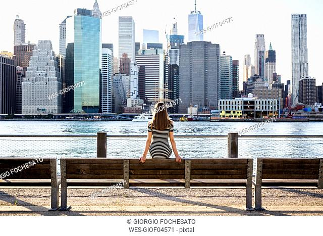 USA, New York, Brooklyn, back view of woman sitting on bench in front of East River and skyline of Manhattan