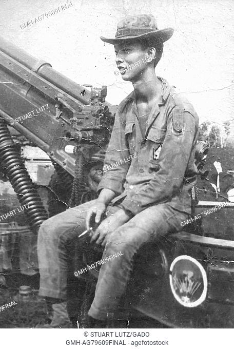 A Vietnamese man who was working for the United States Army sitting on a 105mm Howitzer artillery cannon, Vietnam, 1968