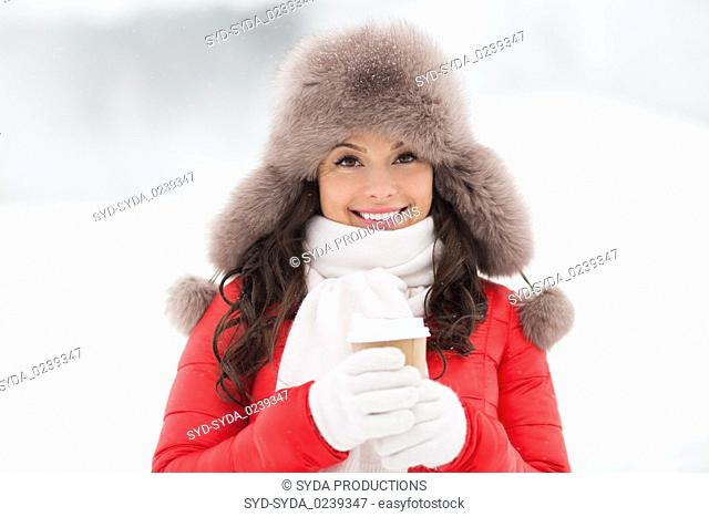 happy woman in winter fur hat with coffee outdoors