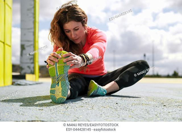 young woman stretching her arms holding your foot on the floor before running
