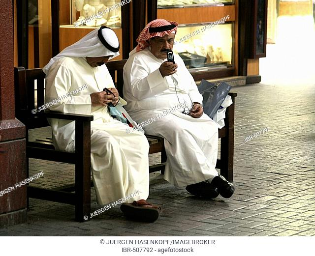 U.A.E., Dubai, two elder men in Arabian clothing sitting on a bench in the Gold Souk, one man with a mobile phone