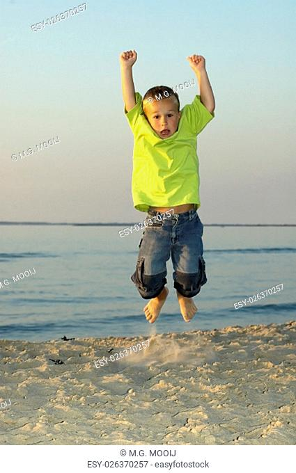 Jumping boy on a beach during sunset