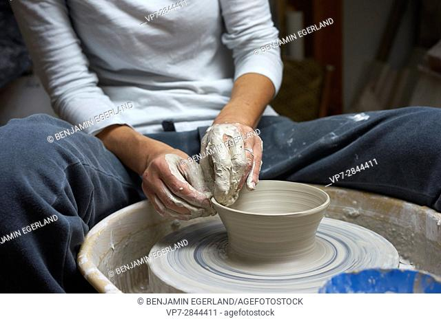hands of a fervent woman creating pottery
