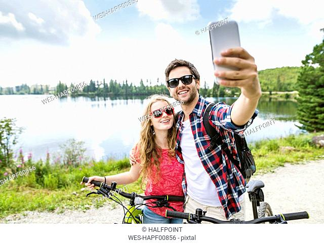 Young couple taking selfies on a bicycle trip