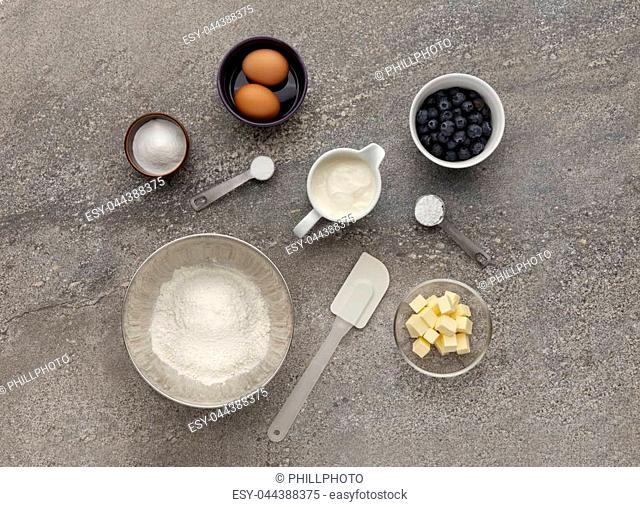 Blueberry muffin ingredient mixture, shot on a stone work surface, inluding eggs, flour, butter and sugar