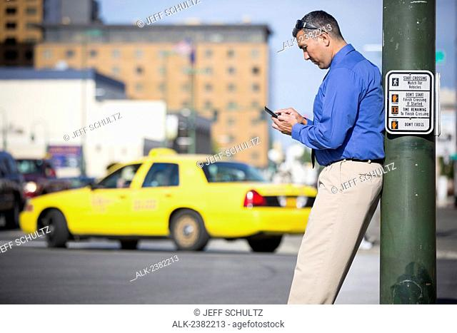 Alaska Native Inupiat businessman using smart phone in downtown street scene, Anchorage, Alaska, Summer