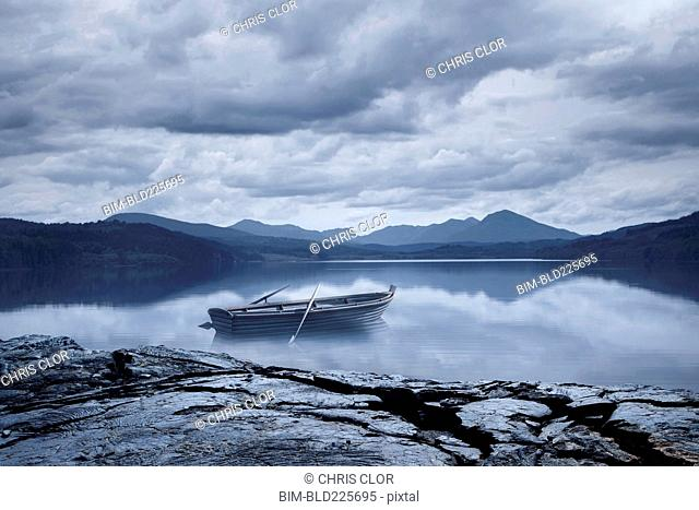 Abandoned rowboat in remote mountain lake