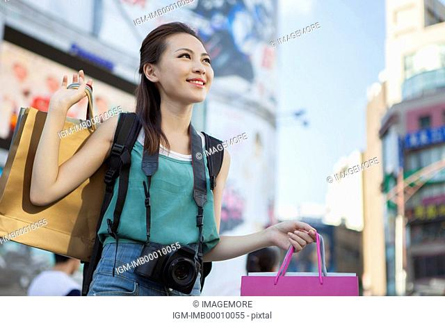 Young woman shopping and travelling with smile
