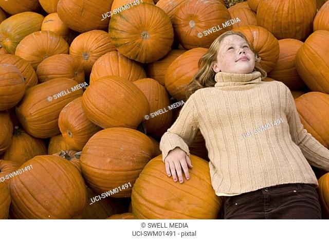 Girl lying on pumpkins