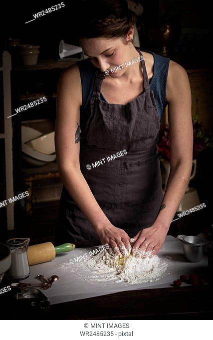 Valentine's Day baking, young woman standing in a kitchen, preparing dough for biscuits