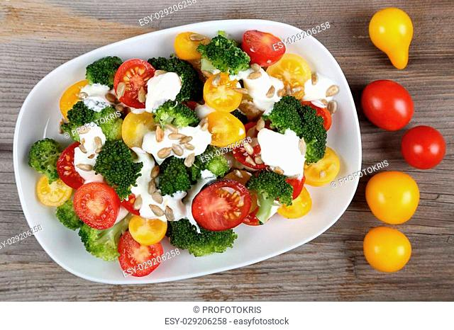 Fresh salad of colorful tomatoes, broccoli, sunflower seeds and garlic dressing