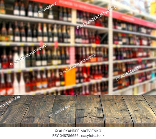 Vintage wooden boards with view to shelves of supermarket. Table top with shopping place. Vintage boards with alcoholic drinks on shelves of shop