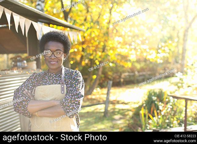 Portrait confident female food cart owner in sunny autumn park