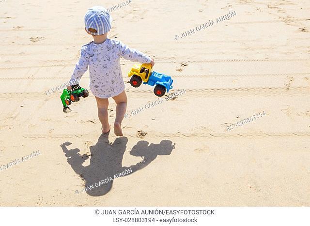 Baby boy walking with toys at the beach. El Rompido, Cartaya, Huelva, Spain